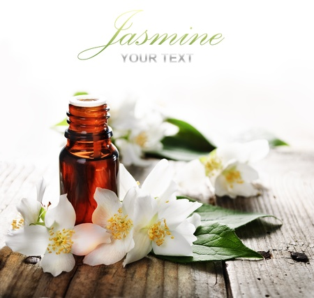 essentials: Essential oil with jasmine flower on wooden plank