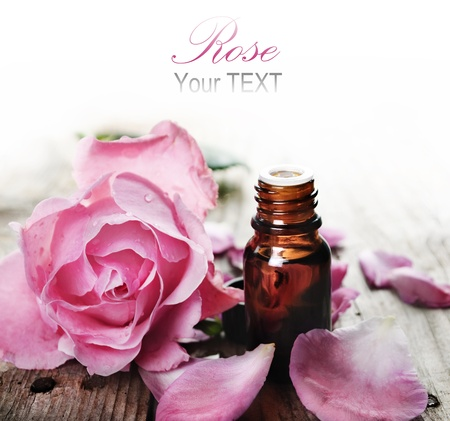 Essential oil with rose petals on wooden background Stockfoto