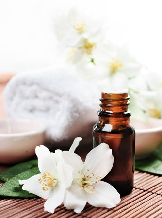 aromatherapy oils: Essential oil with jasmine flower on wooden background