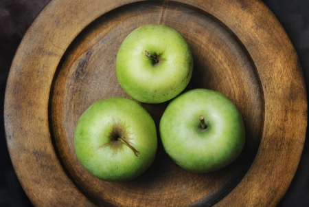 Three green apples in wooden plate photo