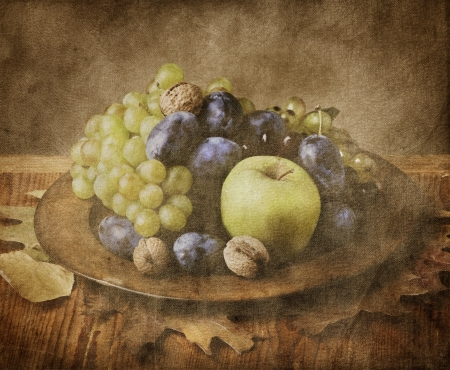 Autumn fruit in wooden plate on grungy background