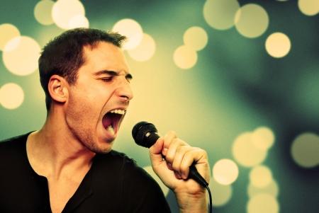cantando: Imagen retra del hombre que canta en el micrófono Foto de archivo