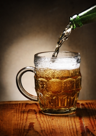 Pouring beer into beer mug photo