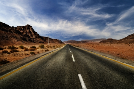 middle of the road: Road in jordanian desert with dramatic sky Stock Photo