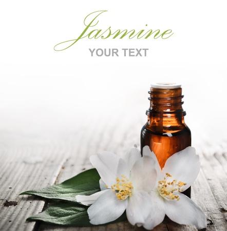 jasmine flower: Essential oil with jasmine flower on wooden plank