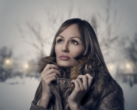 Woman walking in the park on a snowy evening photo
