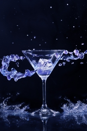 Splashing cocktail over dark background photo