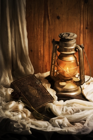 Still life. Lantern, old book and rose. Stock Photo