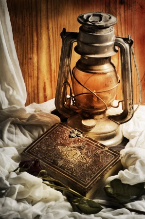 death candle: Still life. Lantern, old book and rose. Stock Photo
