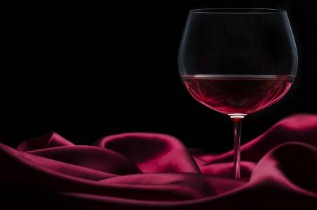 Glass of wine on red silk with dark background