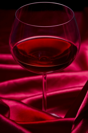 Glass of wine on red silk  photo