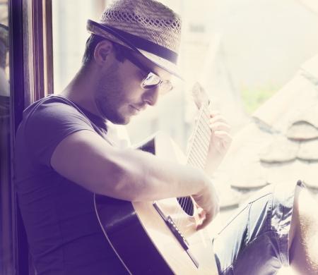라이프 스타일: 젊은 남자가 기타를 연주 창에 앉아