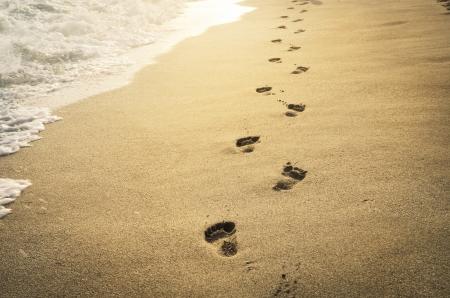 Voetafdrukken in het zand bij zonsondergang