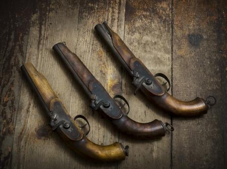 american revolution: Vintage pistols on wooden background Stock Photo