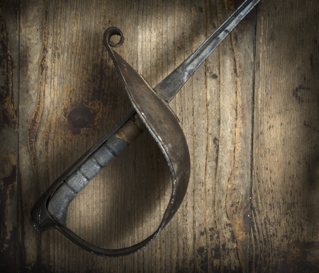 Old fencing sword on wooden background