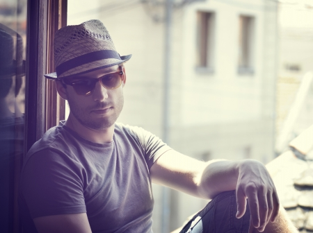 Young man with moder hat and sunglasses photo