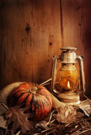 Stilleven. Pompoen, verlichte lantaarn en herfstbladeren.