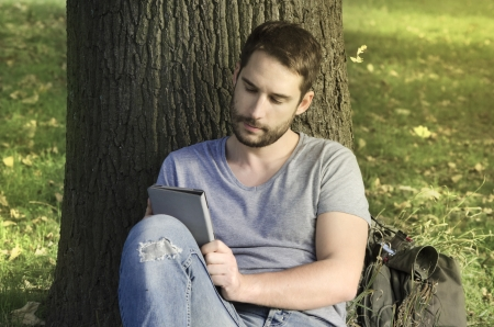 kindle: Young man reading e-book under the tree Stock Photo