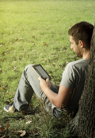 Young man reading e-book in the nature photo