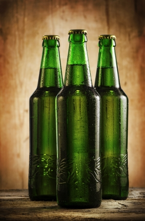 Wet beer bottles on rustic wooden table Stock Photo - 25309729