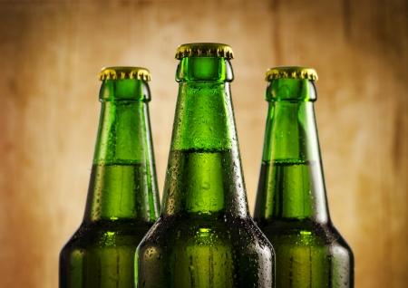 Wet beer bottles on rustic wooden background