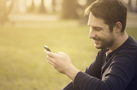 Молодой человек, сидя в парке и текстовых сообщение