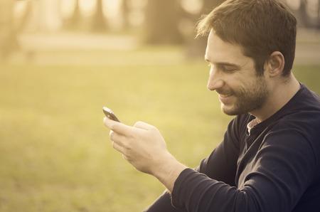 若い男が座っている公園やテキスト メッセージのメッセージ