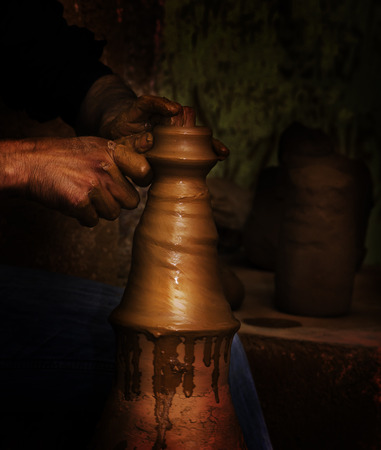 Potter shaping clay on the pottery wheel photo