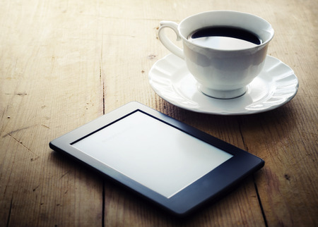 beverage display: E-book reader and coffee cup on wooden table