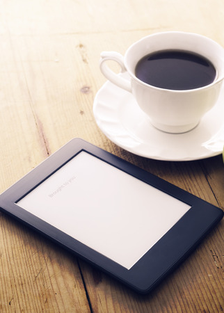 kindle:  E-book reader and coffee cup with morning light