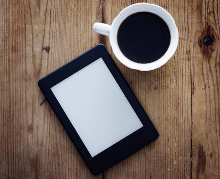 나무 테이블에 전자 책 리더와 커피 한잔 스톡 콘텐츠