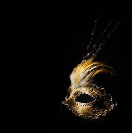 Golden venetian mask over black background