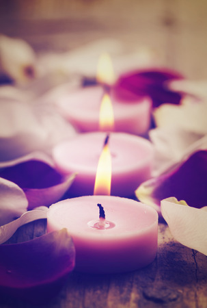 Spa candles and rose petals. Retro filter. photo