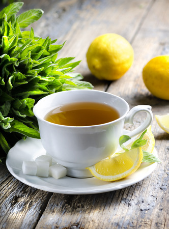 Cup of tea with mint and lemon slices. photo