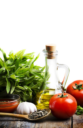 Olive oil, tomato and herbs over white background photo