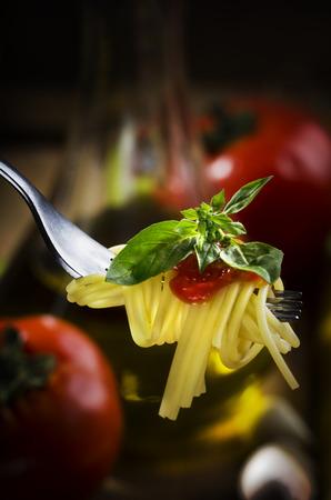 Spaghetti, tomato sauce and basil on fork