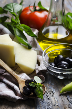 Cheese, olives, basil, tomato and olive oil on wooden table photo