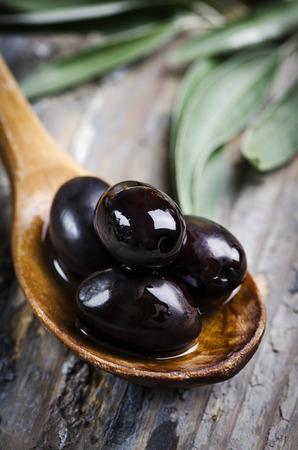 Black olives in wooden spoon photo