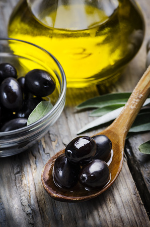 Olives and olive oil on wooden table photo