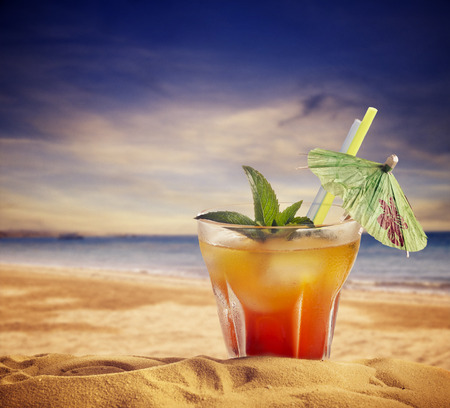 Cocktail and sandy beach. summer concept.