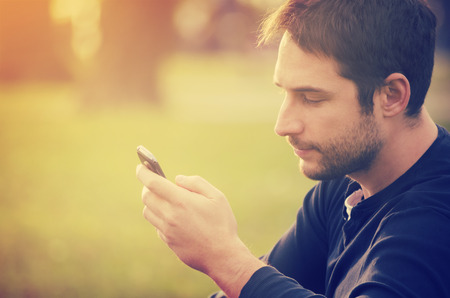 adult texting: Young man sitting in the park and texting a message Stock Photo