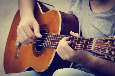 남자는 거리에서 기타를 연주. 복고 스타일입니다.