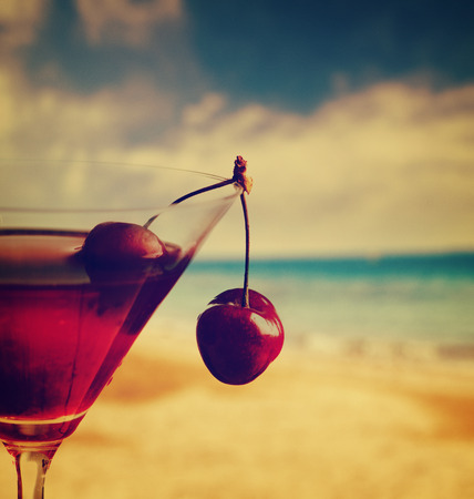 Cherry cocktail on the beach in retro style 스톡 콘텐츠