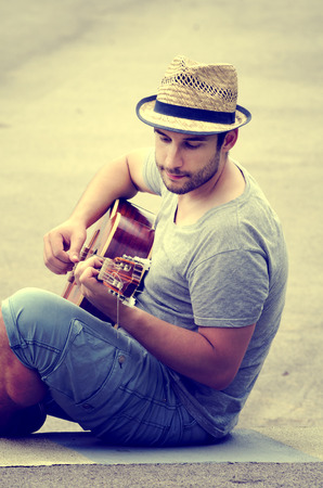 man plays the guitar on the street. retro style. photo