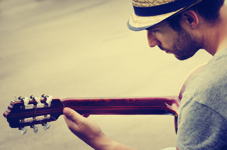 男は路上でギターを果たしています。レトロなスタイル。 写真素材