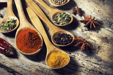 Colorful spices on rustic wooden table photo