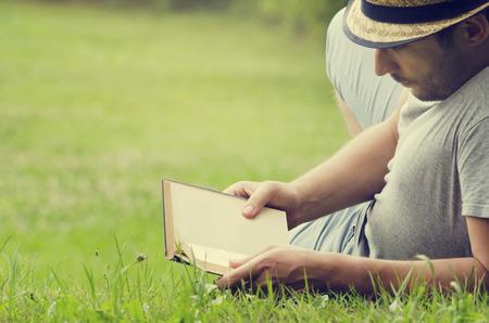 Человек читает книгу на траве Фото со стока