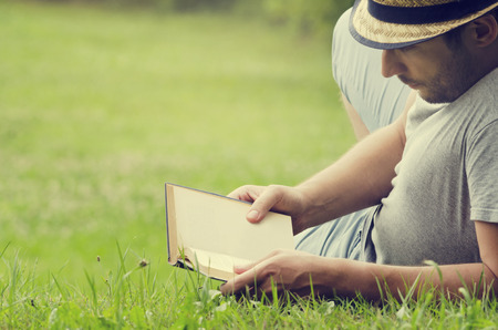 lying:  Man reading a book on the grass Stock Photo
