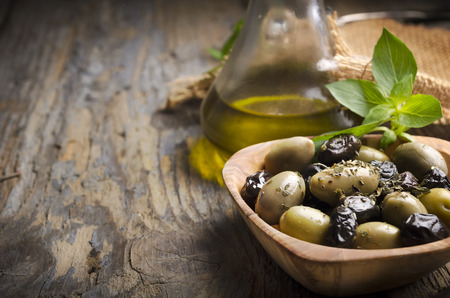 Olives and olive oil on rustic wooden table photo