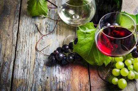 ワイングラスと素朴な木製のテーブルでブドウ